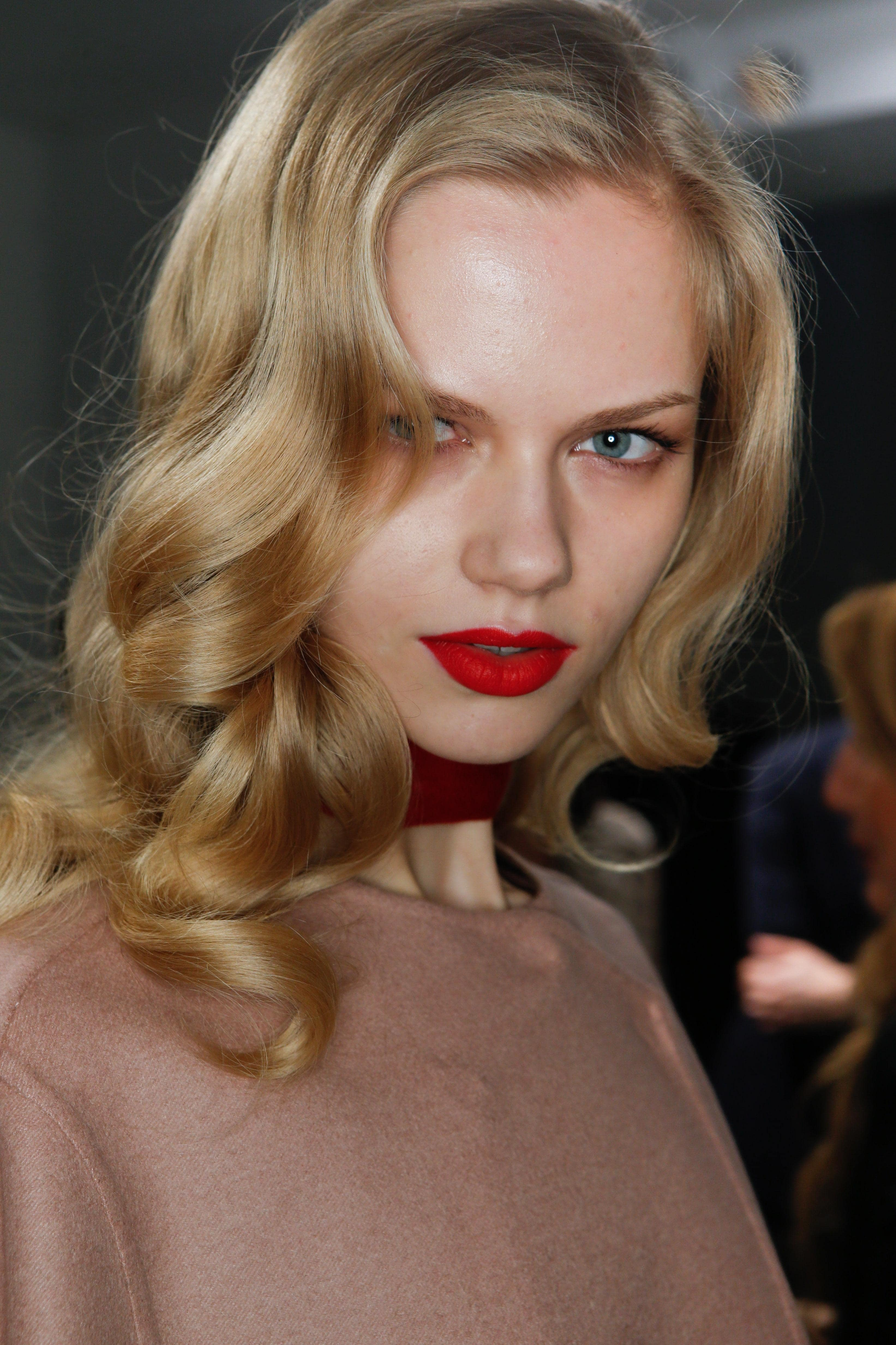 Party hairstyles: Woman with medium length vintage curly blonde hair wearing a soft pink top and bold red lipstick.