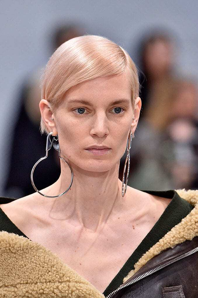 Shades of blonde hair: Model with pink toned blonde straight hair styled in a side parted updo wearing large hoop earrings on runway.