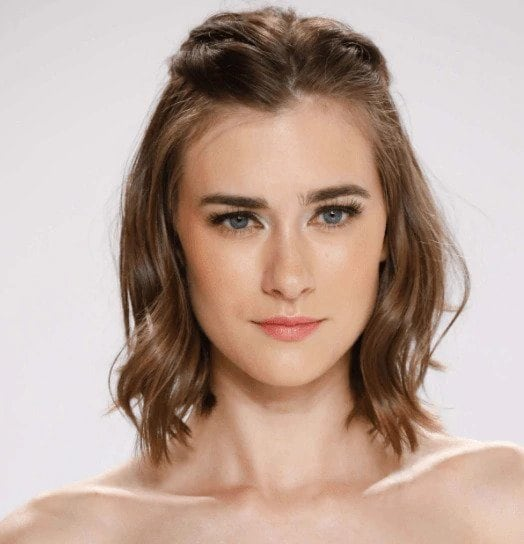 Party hairstyles: Woman with shoulder length brown hair with soft waves pinned back at the top.