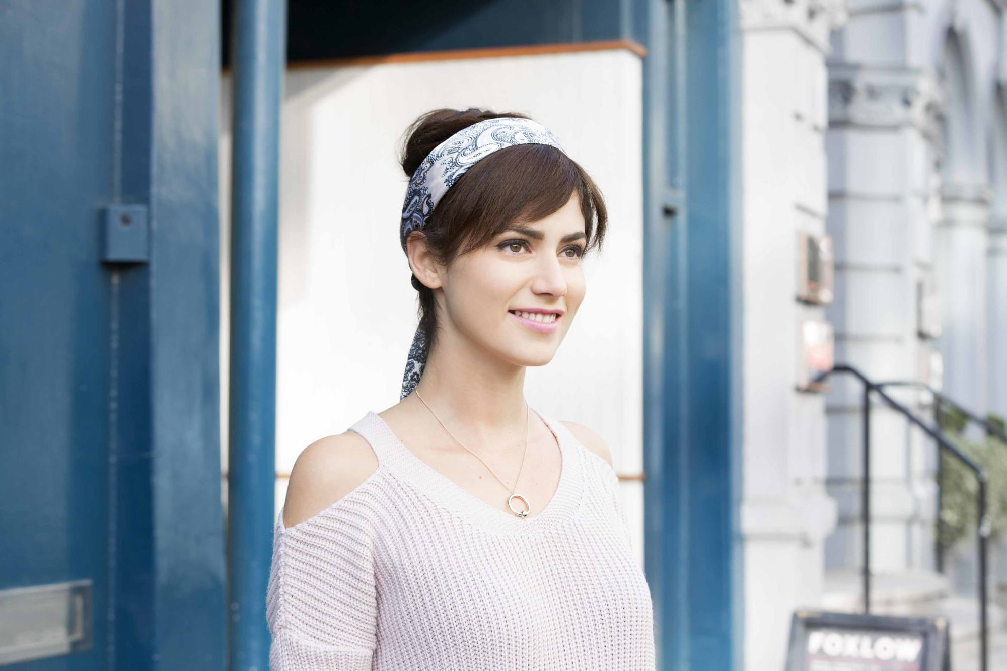 Party hairstyles: Woman with dark brown straight hair styled in a high updo with side fringe wrapped with a blue and white headscarf wearing a cold shoulder knitted top.