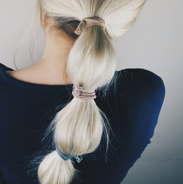 blonde woman with a bubble pony wrapped in ribbon hair ties