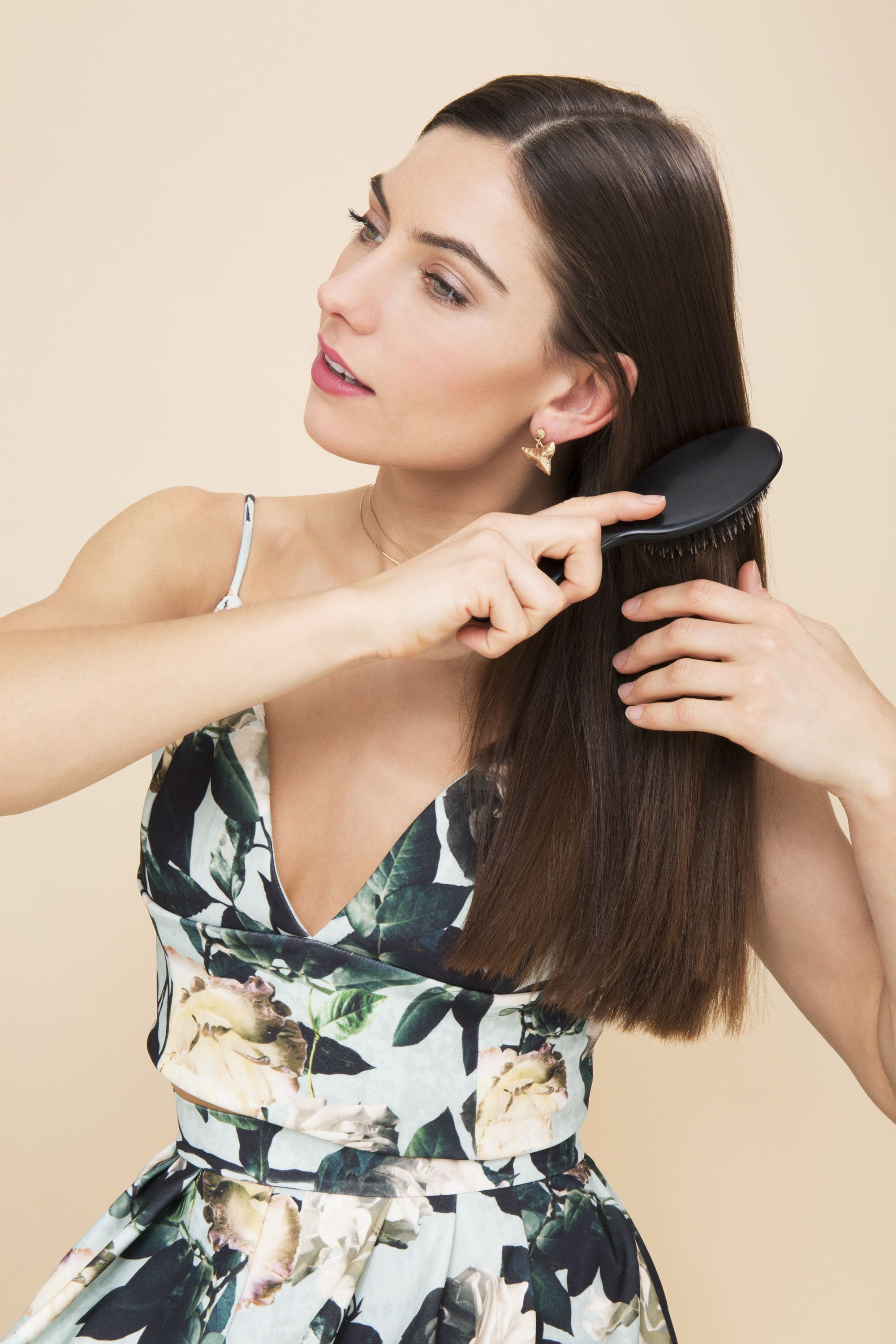brunette model in a floral dress brushing her hair with a paddle brush