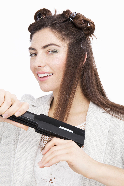 brunette model using straighteners to straighten her hair