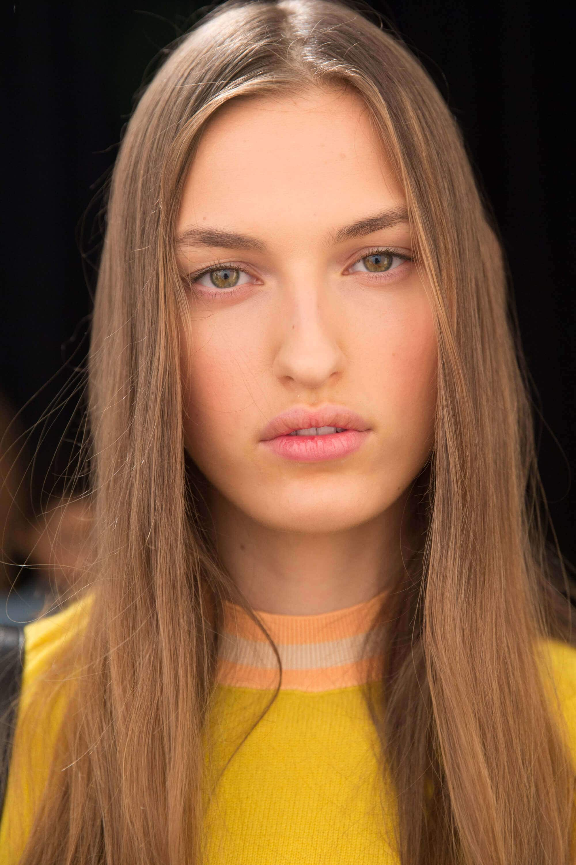 Party hairstyles: Model with long straight dark blonde hair wearing a yellow jumper.
