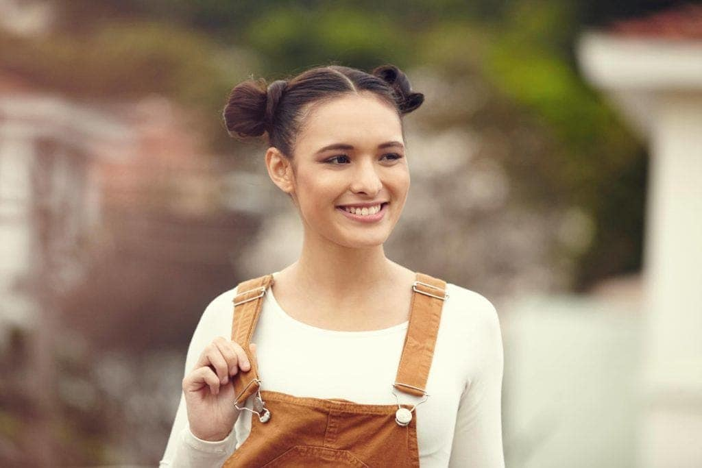 Party hairstyles: Woman with brown straight hair styled in high space buns updo wearing dungarees.