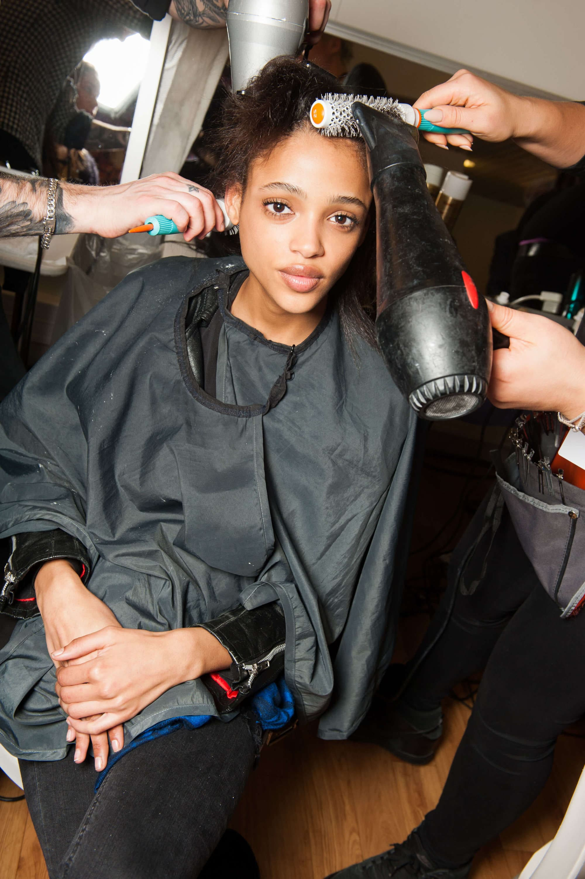 best brush for curly hair: close up shot of model backstage having her curly hair done with a round hair brush