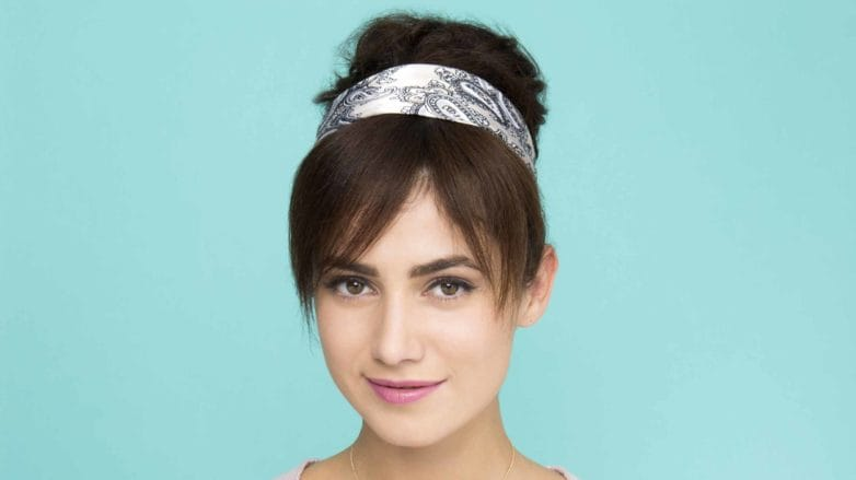 a cute woman with topknot hairstyle on the blue background