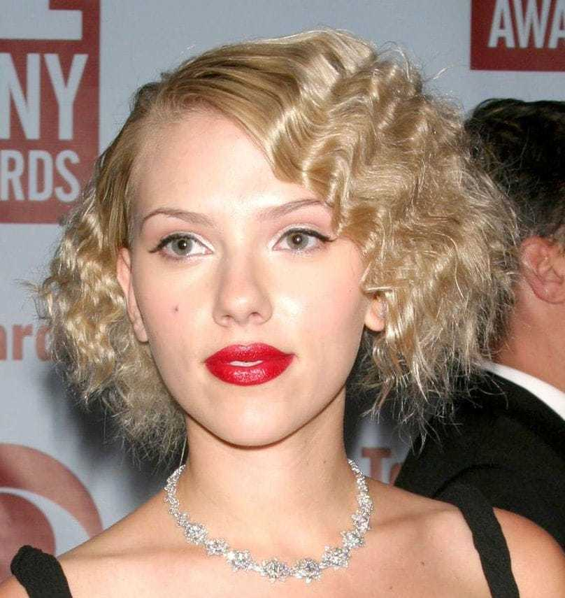 Crimped hair: Scarlett Johanson with short blonde wavy hair with bold red lips.