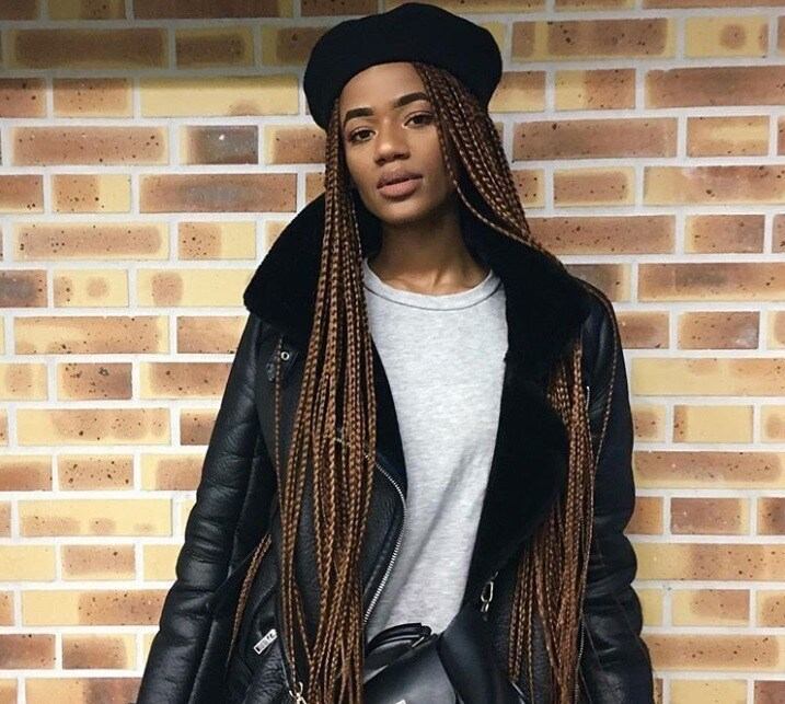 protective hairstyles: close up shot of woman with braids and beret, posing outside and wearing black jacket
