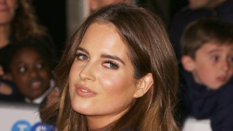 Side view of Binky Felstead with medium brown balayage long hair with waves