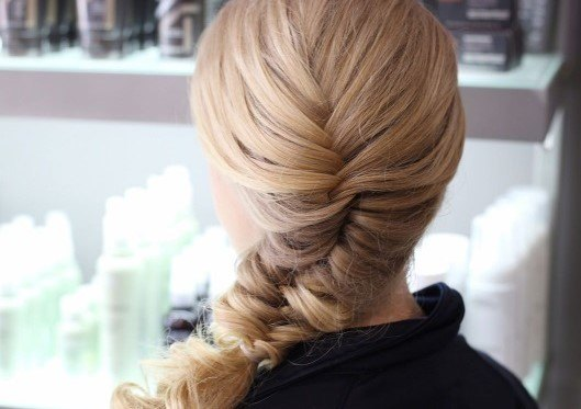 blonde woman with a side fishtail braid hairstyle