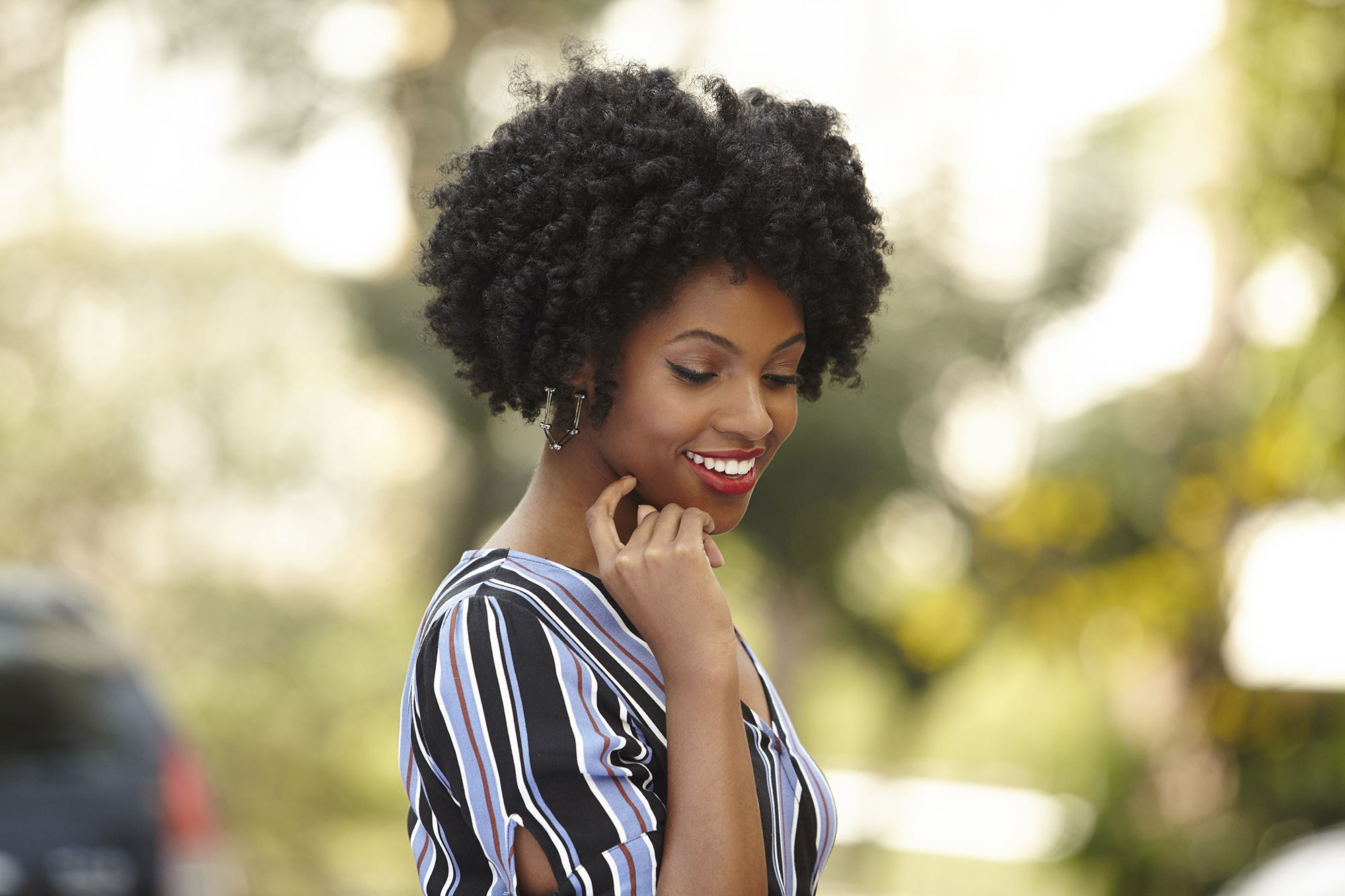 low manipulation hairstyles: close up shot of black model with heatless curls posing outside