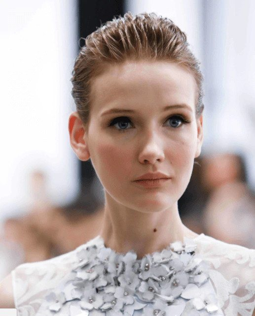 Party hairstyles: Woman with blonde short hair styled in a wet look slicked back style wearing a white lace dress.