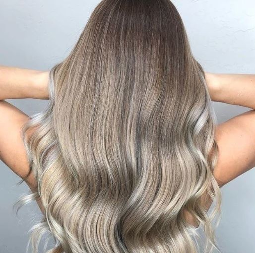 Shades of blonde hair: Woman with long wavy ash blonde balayage hair running her hands through her hair.