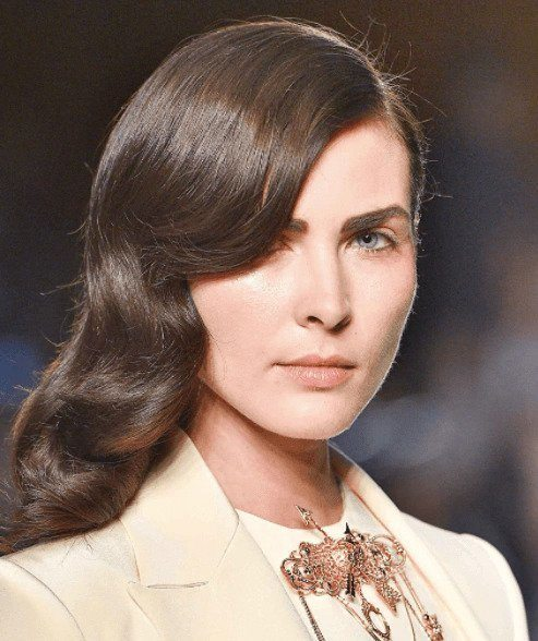 Party hairstyles: Woman with vintage style curls on medium brown shoulder length hair on catwalk.