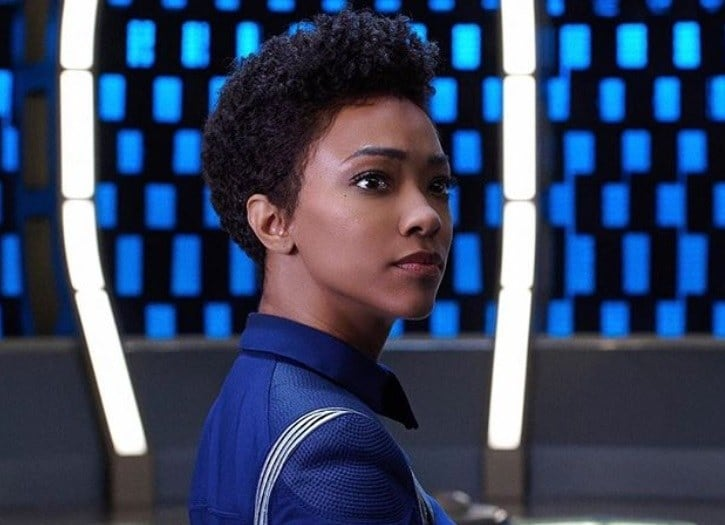 close up shot of sonequa martin-green with short natural curly hair on the set of the star trek discovery, wearing blue suit