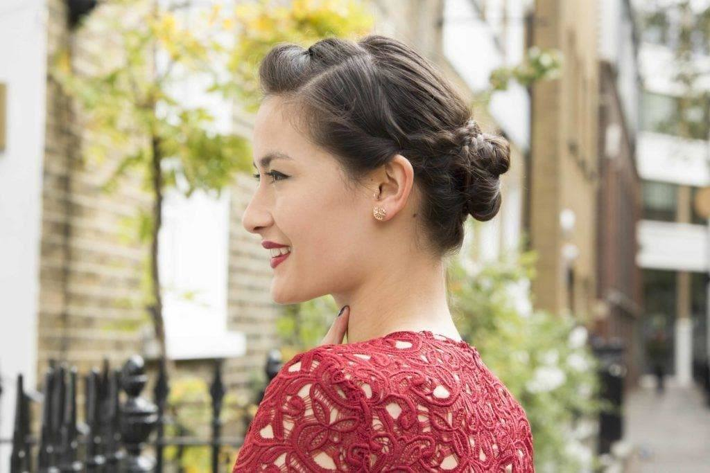 Party hairstyles: Woman with dark brown hair styled ina braided bun wearing a black lace top.