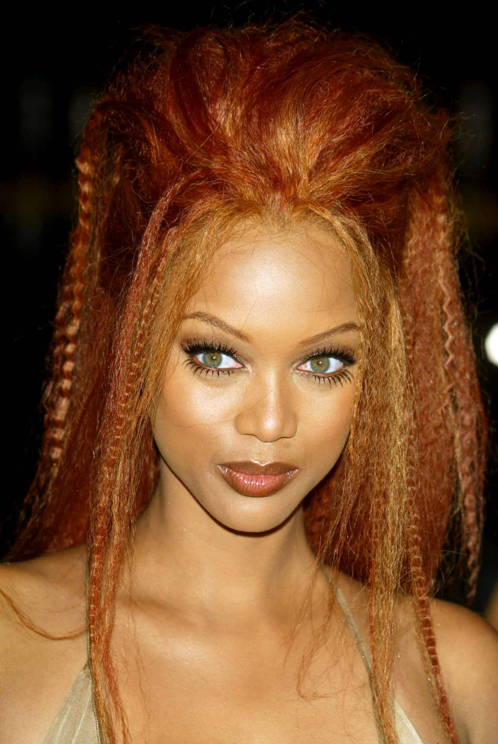 Crimped hair: Tyra Banks with copper red long crimped hair in updo ponytail.