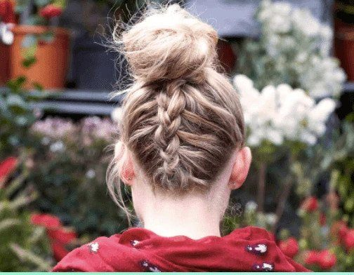 Party hairstyles: Back view of woman with blonde highlight hair in upside down braided bun wearing a red top.