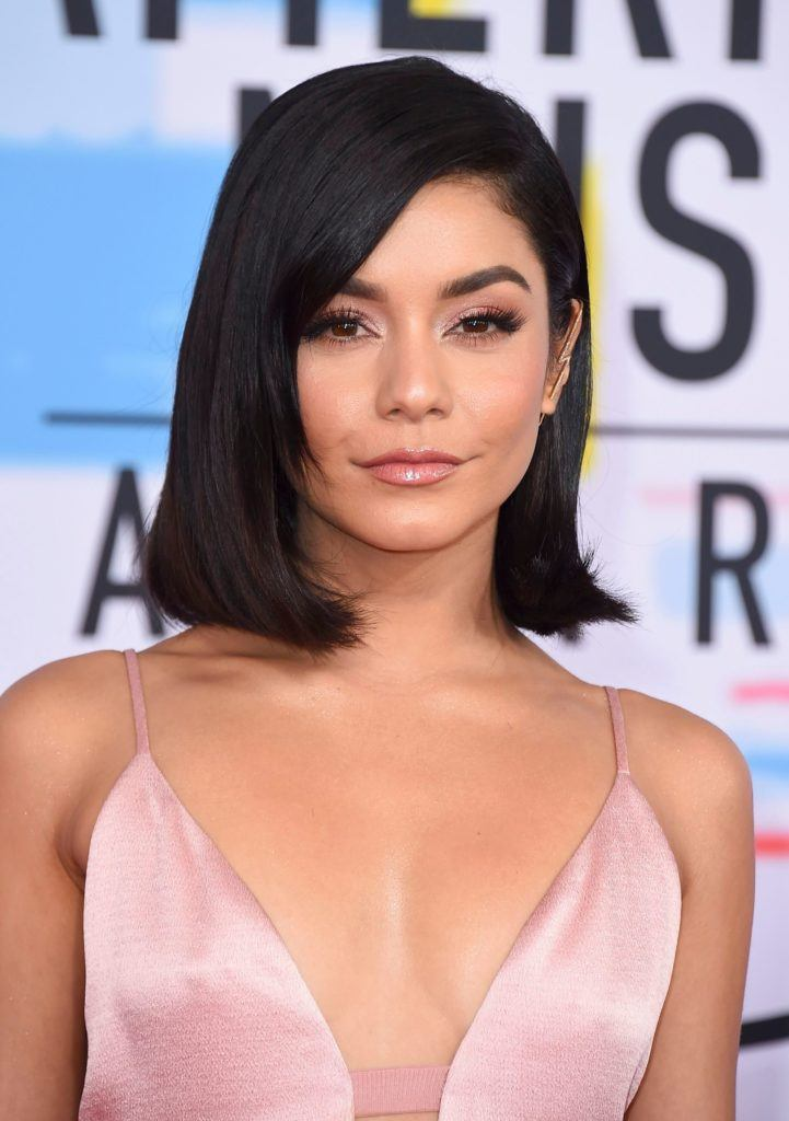 American Music awards 2018: Vanessa Hudgens with straight, dark brown long bob with a side sweep and flipped out ends, wearing a satin pink dress on the red carpet