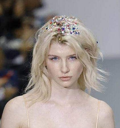 Party hairstyles: Woman with shoulder length bleach blonde hair with glitter roots on catwalk runway.
