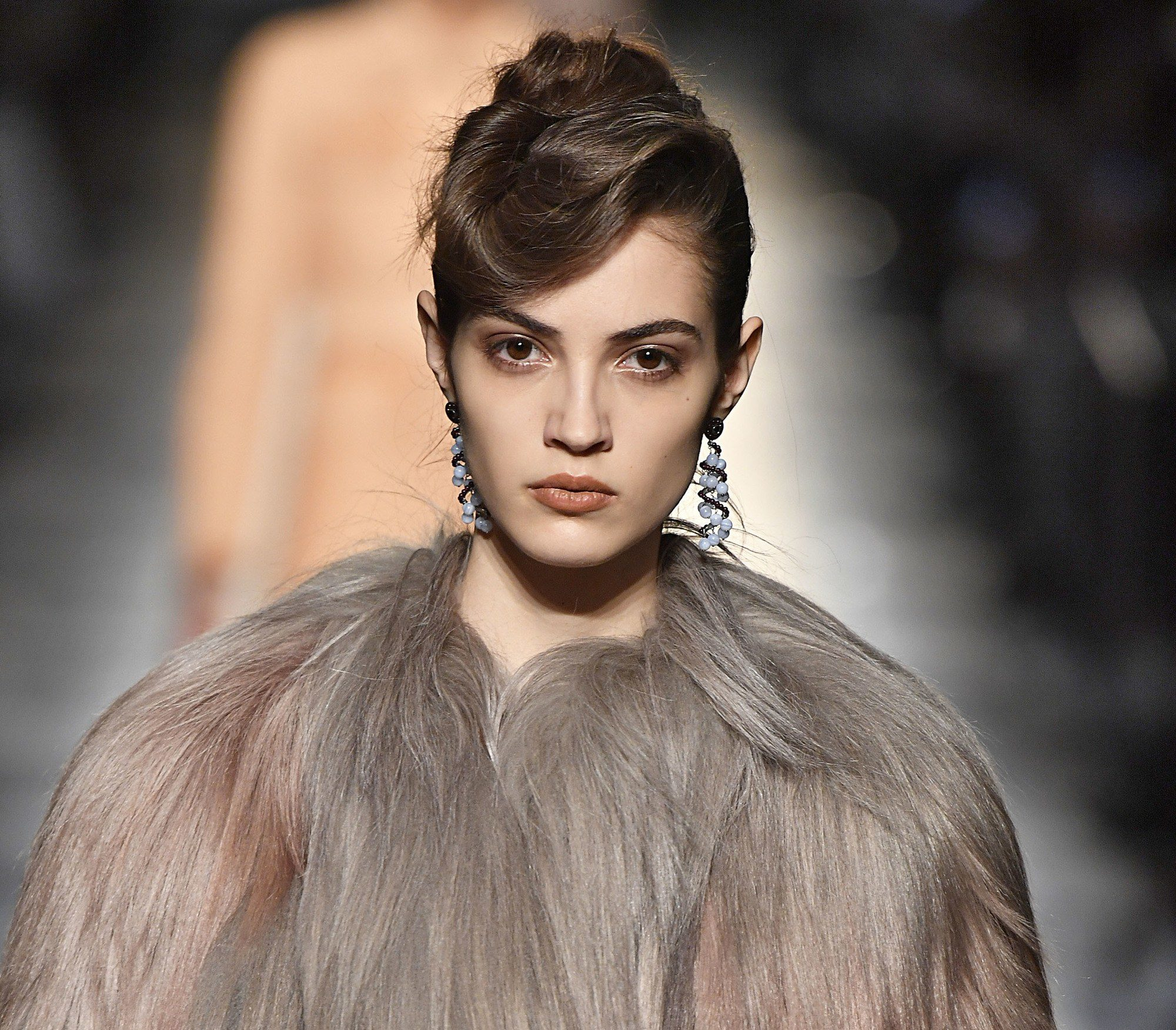 Vintage updo hairstyles: Close up shot of woman with an undone quiff hairstyle styled into an updo walking on the runway