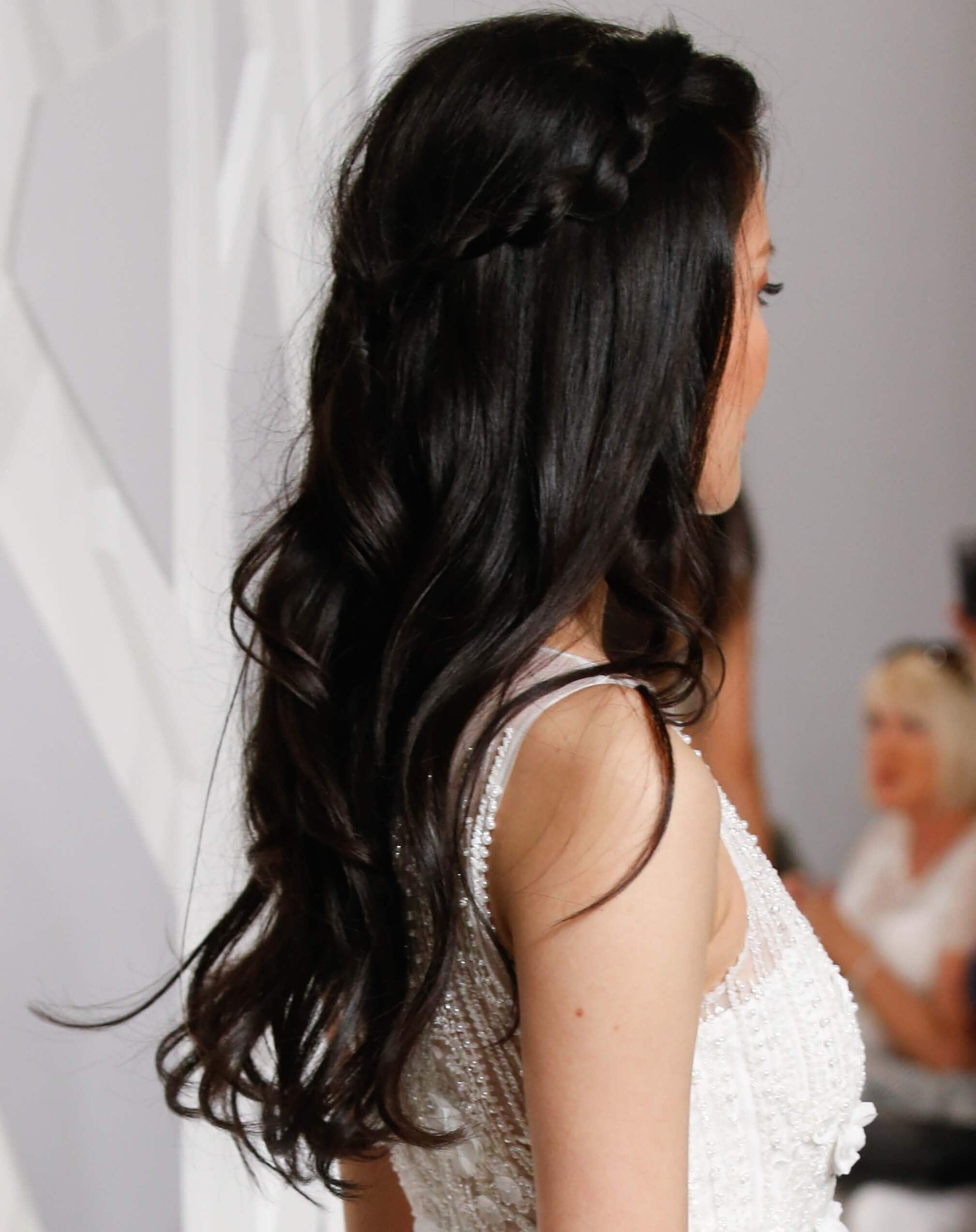 Party hairstyles: Woman with long wavy brown hair in half-up, half-down style with accent braids wearing a white dress.