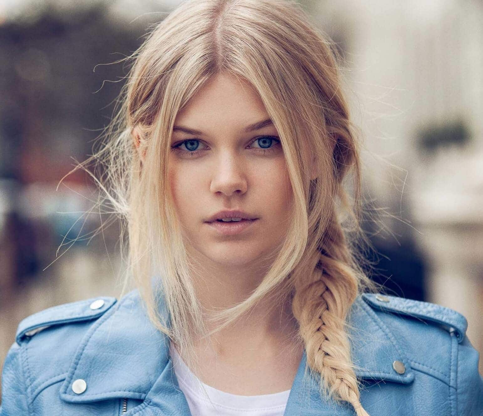 Party hairstyles: Woman with straight light blonde hair in side braid wearing a light blue leather jacket.