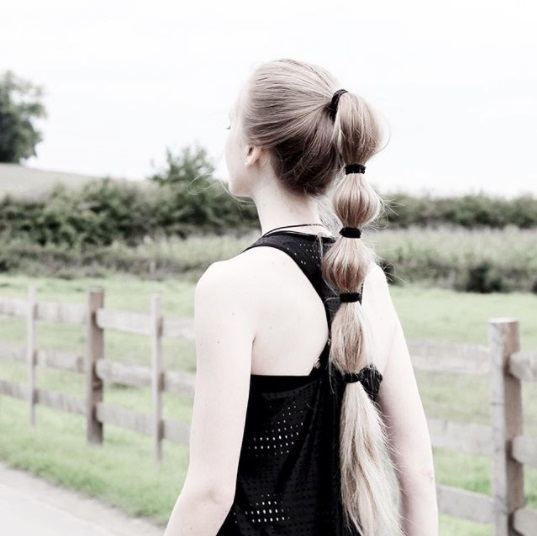 blonde woman wearing workout clothes with her hair in a bubble ponytail