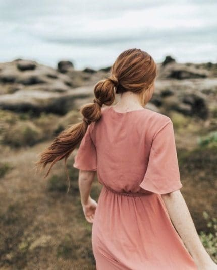 redhead woman in a pink dress with her hair in a bubble ponytail hairstyle