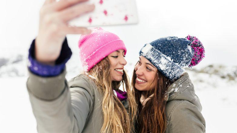 close up shot two women in the snow with jackets, with wavy hair and winter hats taking a selfie