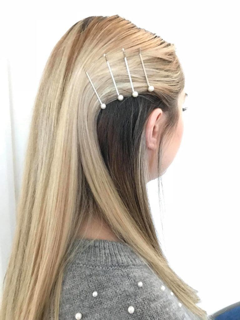 all things hair editor beth wearing a pearl grey jumper with pearl hair slides in her blonde hair