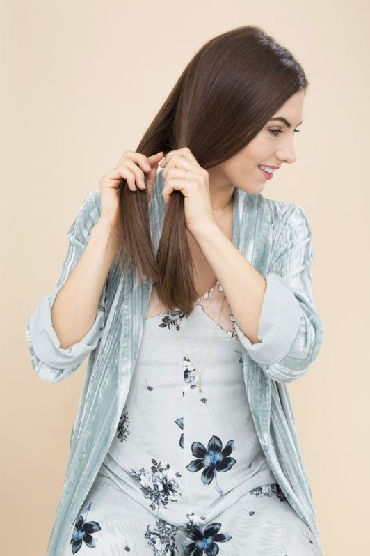 How to fishtail braid: Woman in a studio about to fishtail braid her hair in a studio setting