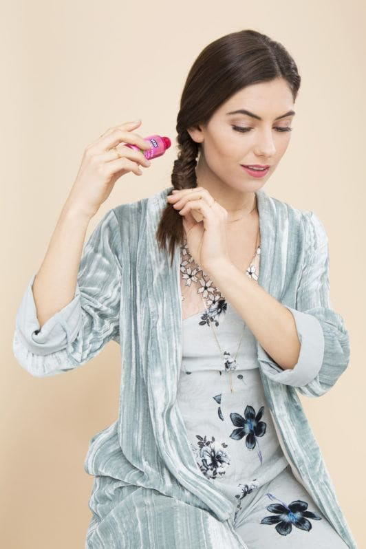 Fishtail braid how-to: Shot of woman with a fishtail braid, sprinkling volumising powder on her braid