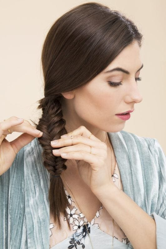 How to do a fishtail plait: Shot of woman pancaking her dark brown fishtail plait in a studio setting