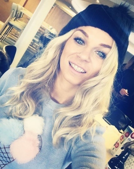 Woman with long curly blonde hair with a black bobble hat