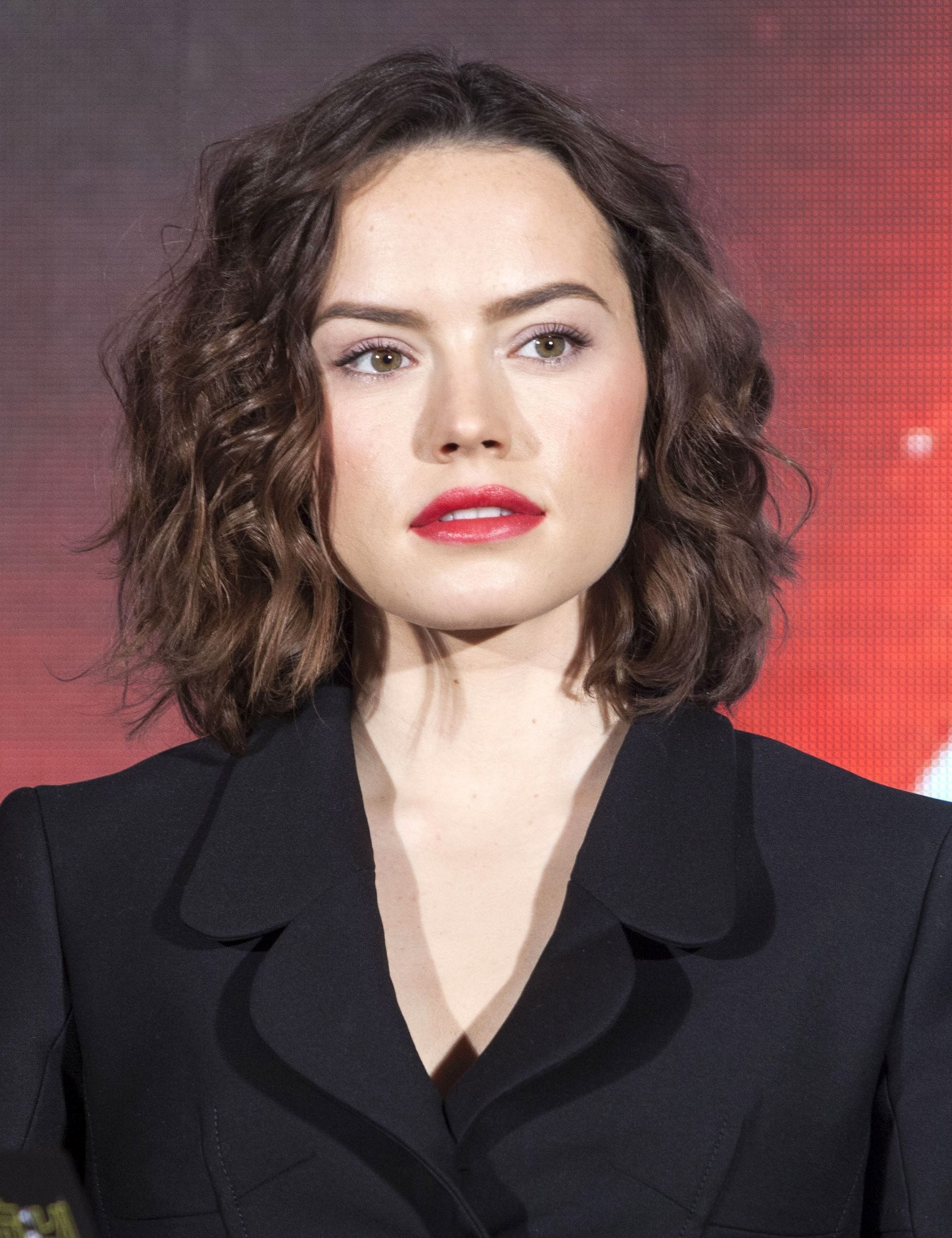 front view of daisy ridley with brown curly shoulder length hair