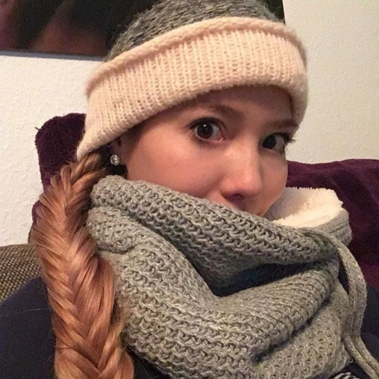 Brunette woman wearing a grey hat and scarf with her hair in a side fishtail braid