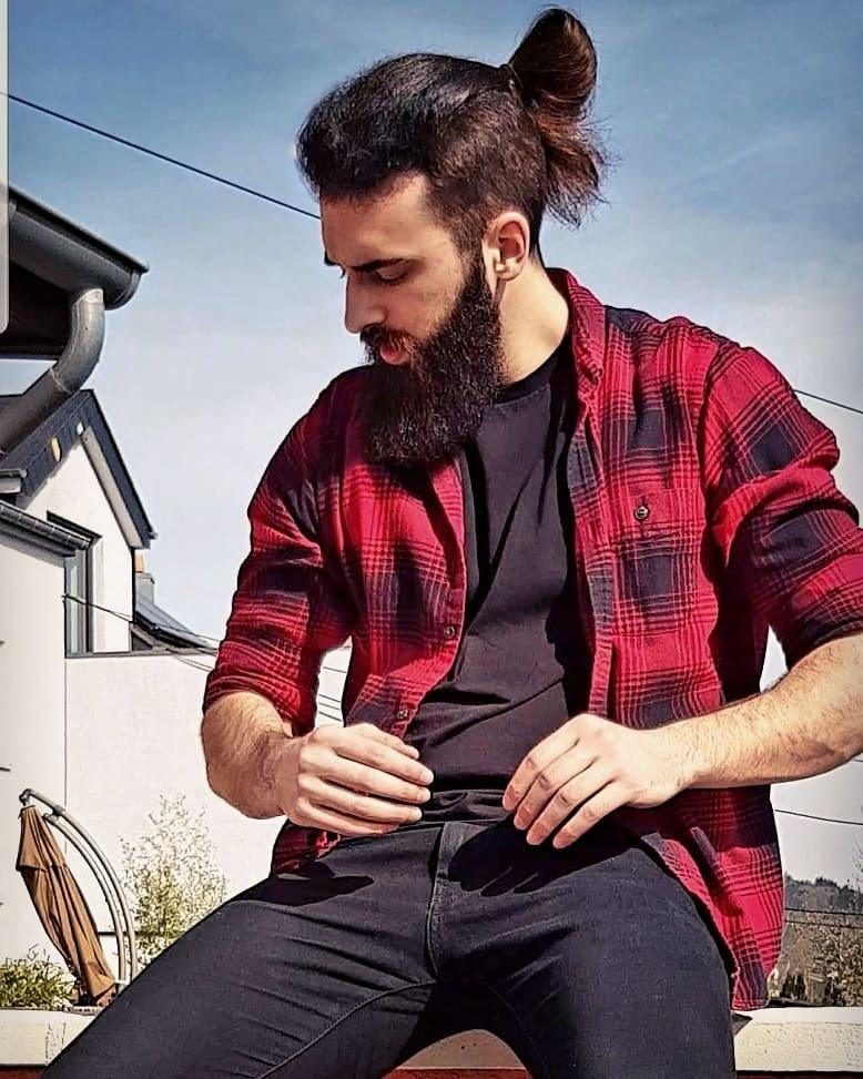 Man with an overgrown long undercut hairstyle with beard