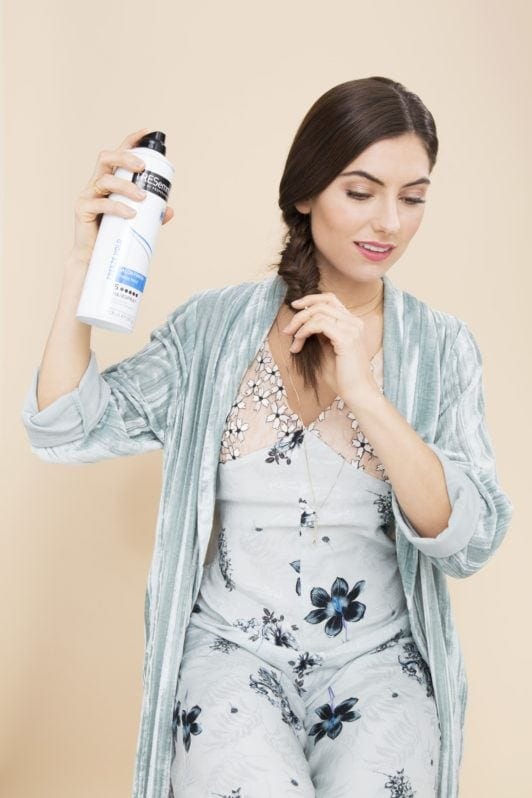 How to do a fishtail braid: Shot of woman with a dark brown fishtail plait in a studio setting, spraying hairspray on it