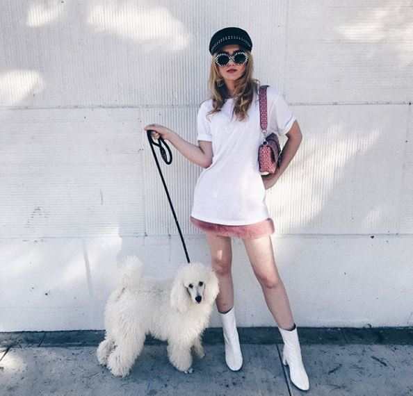 front view of kathryn newton with blonde long hair under baker boy cap holding dog
