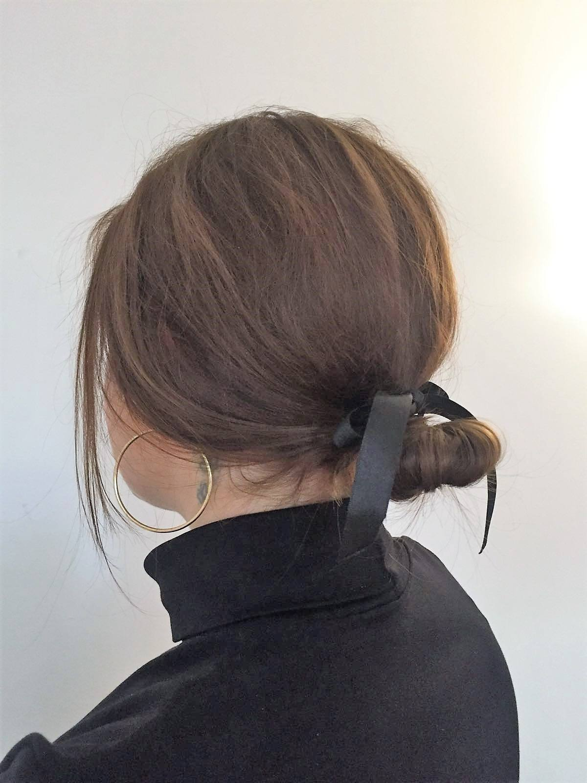 close up shot of woman with short hair that's styled into a low bun with a bow around it, wearing black top and hoop earrings