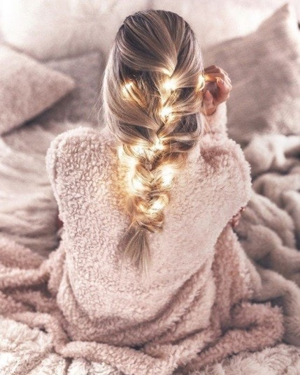 blonde woman with long hair in a big french braid with fairy lights in
