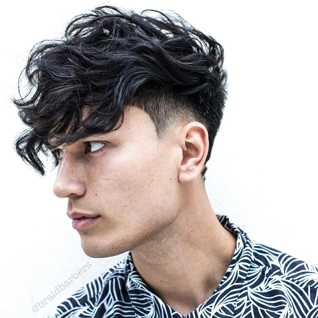 Man with long curly fringe and low undercut fade