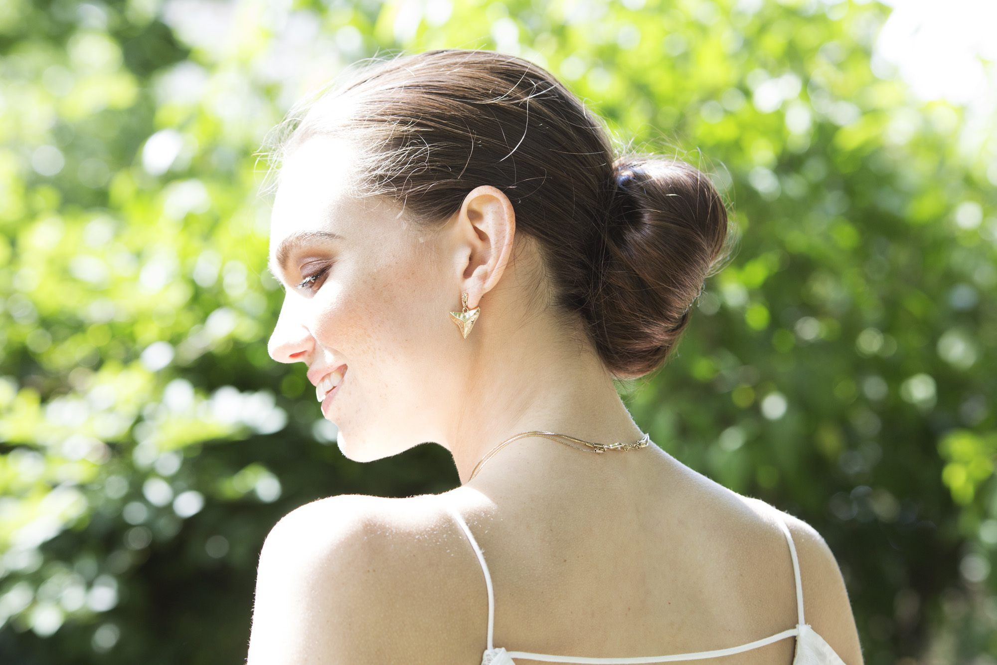 back shot of model with ballerina low bun updo hairstyle, wearing white and standing outside in a park