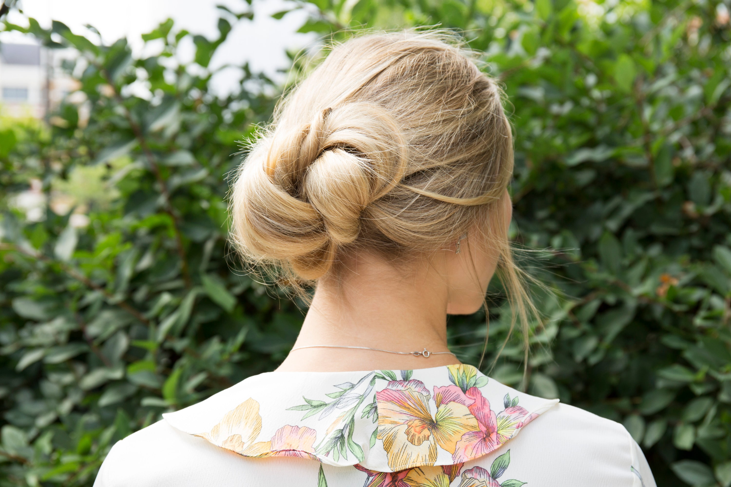 low bun hairstyles: close up shot of model with banana bun hairstyle, wearing floral dress