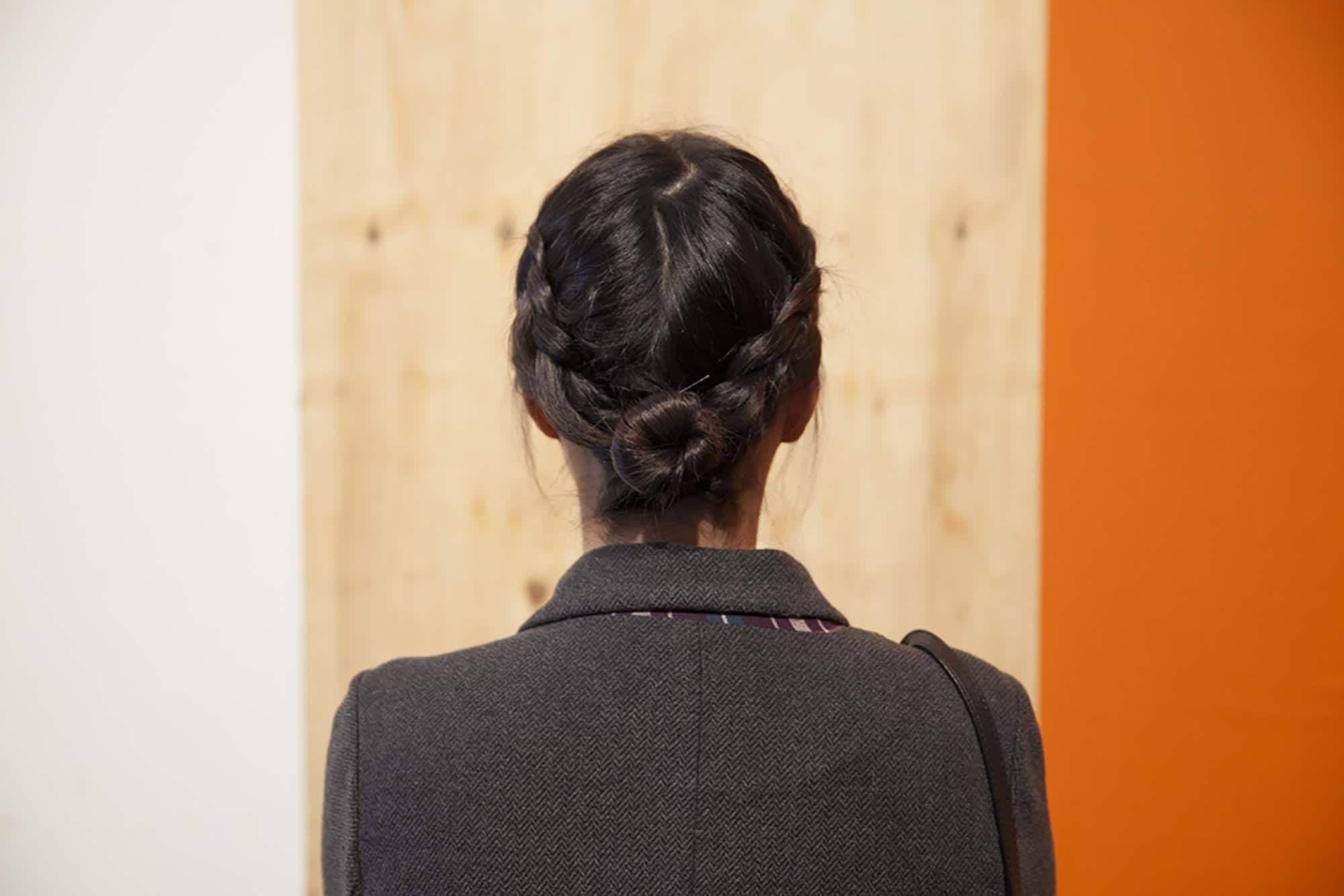 back shot of model with braided low bun updo hairstyle, wearing black jacket