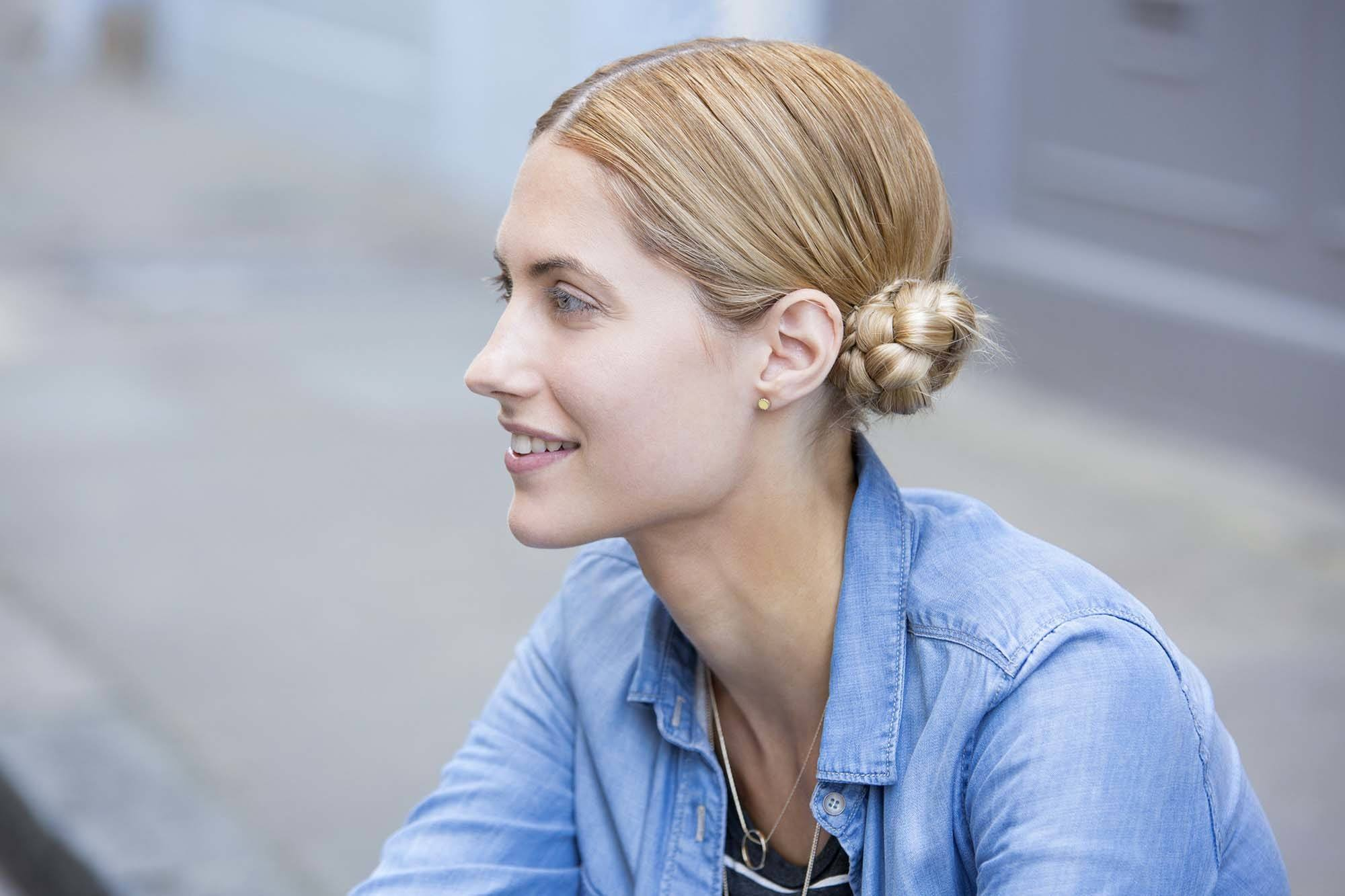 close up shot of model with low macaron buns hairstyle, wearing denim outfit street style