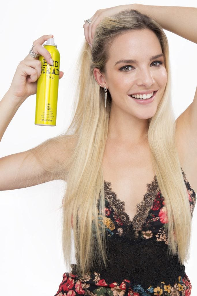 How to do a messy bun with long hair blonde girl spraying dry shampoo smiling
