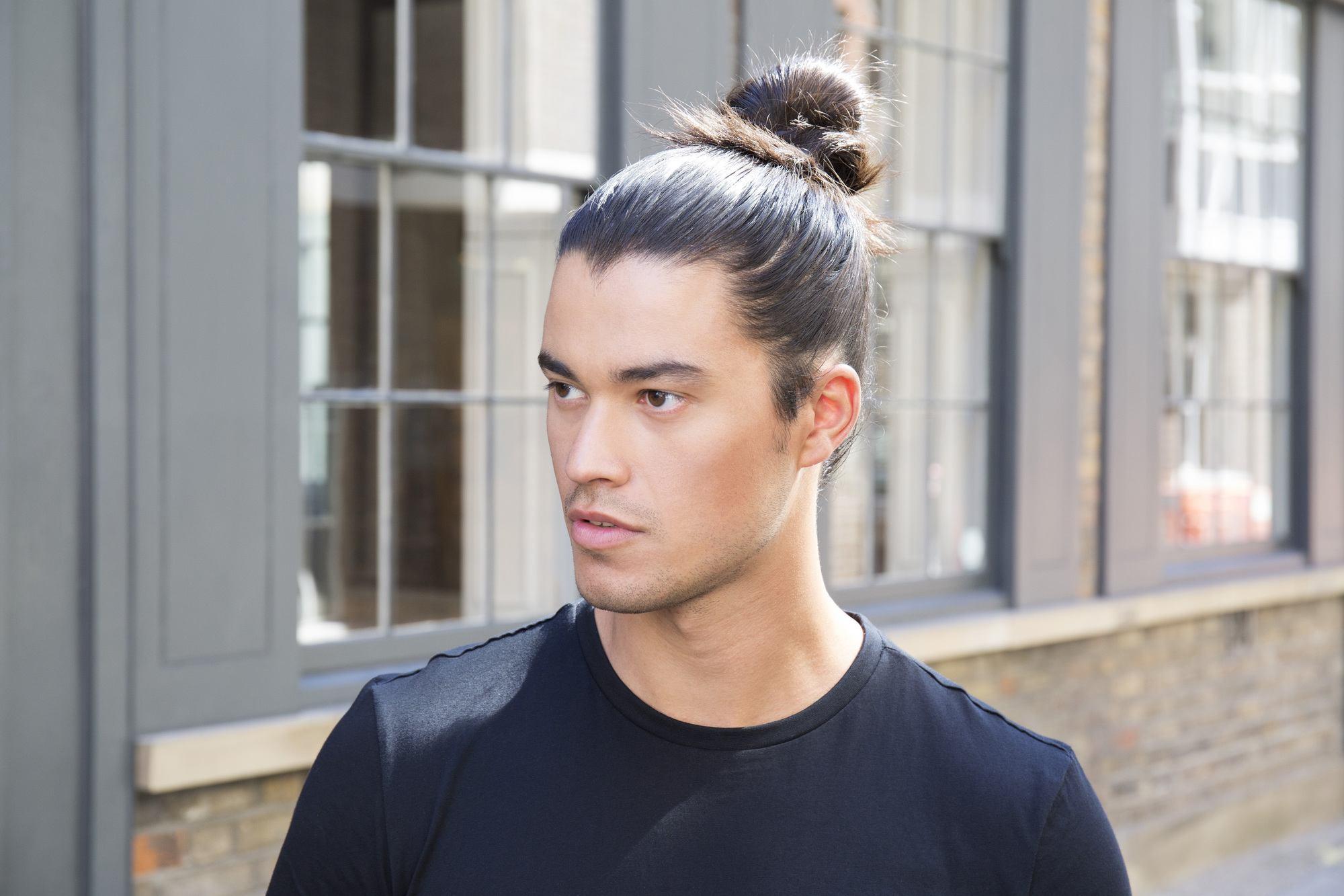 Man bun tutorial brunette man looking away from camera standing in street